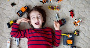 Toddler boy on his back laughing surrounded by toys